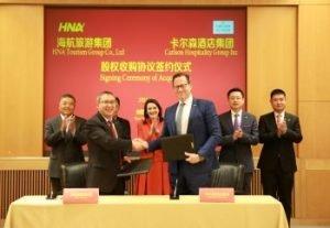 Bai Haibo, Chairman and CEO, HNA Hospitality Group (links vorne) und David P. Berg, CEO, Carlson Hospitality Group bei der Vertragsunterzeichnung. Bild: Carlson Hospitality Group