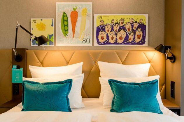 Über dem Bett befinden sich stilisierte Briefmarken. Bild: Motel One
