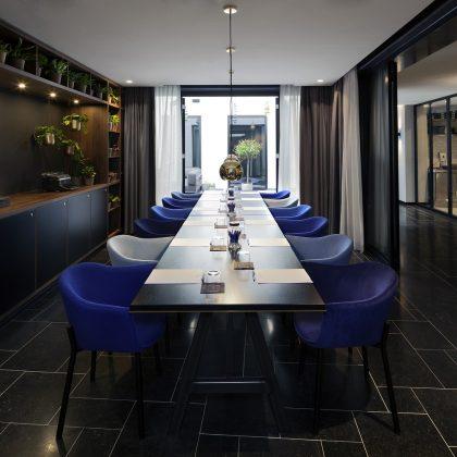"""Im Tagungsraum """"Garden Room"""" finden sich Grünpflanzen und eine Fensterfront zum Garten. Den Bezug zum Hintergrund des Bauwerks schaffen tintenblaue Farbtupfer und eine Schreibmaschine. Bild: Ewout Huibers"""
