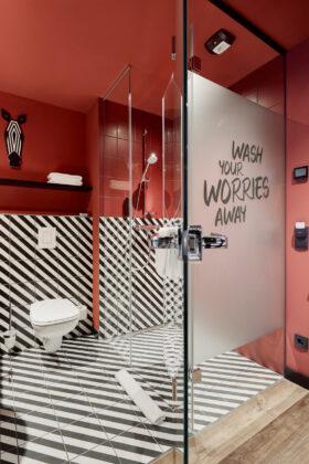 """Ein Badezimmer mit roten Wänden, auf dem Boden und an der Wand befinden sich in schwarz-weiße, schräg gestreifte Fliesen. Auf einer der Glaswände der Dusche steht """"Wash your worries away"""""""