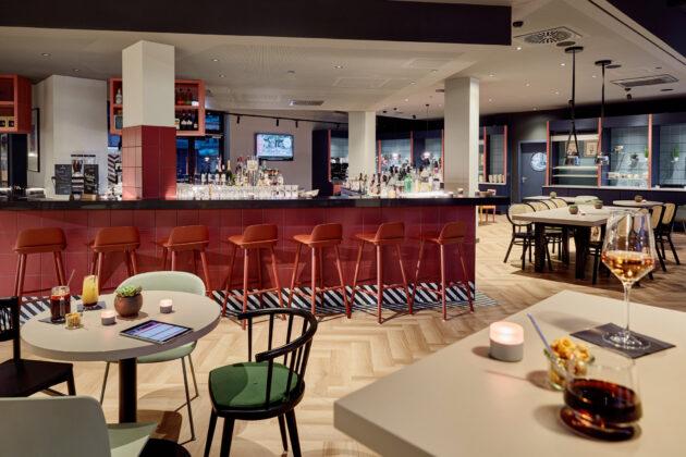 Ein öffentlicher Bereich im Hotel LÉGÈRE EXPRESS, Leipzig. Im Zentrum ist ein Barteresen in rot. Außerdem gibt es noch Sitzgruppen und Esstische.