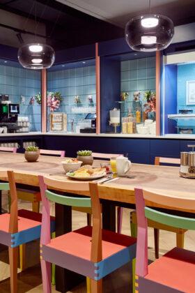 Ein offener Gastronomiebereich, ein langer Holztisch mit bunten Stühlen. An den Wänden stehen eine Kaffeemaschine, Gläser und verschiedene Spender für Müsli.