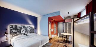 Ein Hotelzimmer, rechts steht ein Stockbett, im Zentrum ein Doppelbett mit hellgrauem Bezug. Die Wände sind in Blao, hellblau und rot gestrichen. Auf dem Boden liegt ein geometrisch gemusterter Teppich in schwarz-weiß.